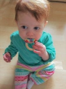 picture of baby chewing on wood ring teether