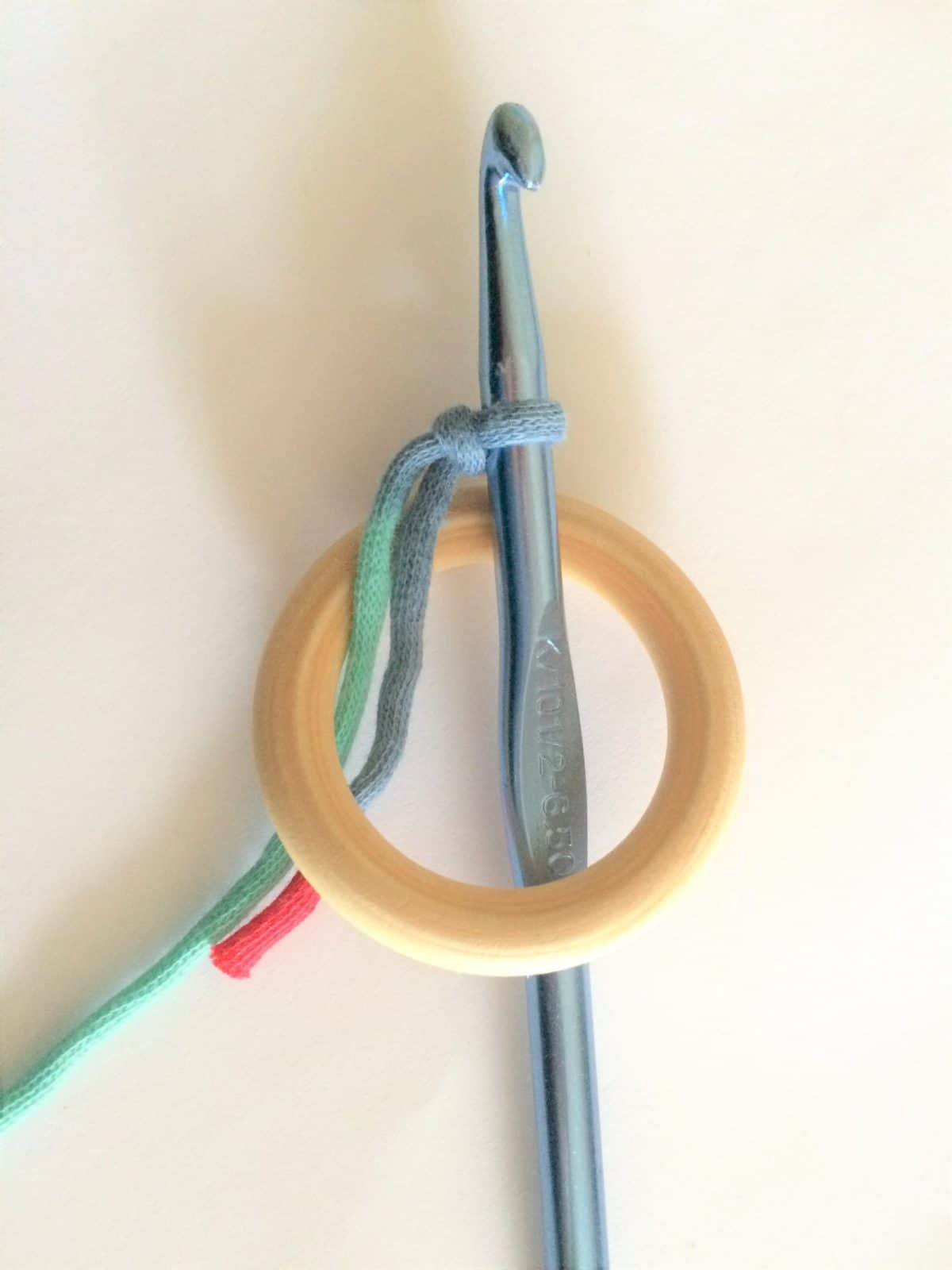 Crochet hook through wooden ring.