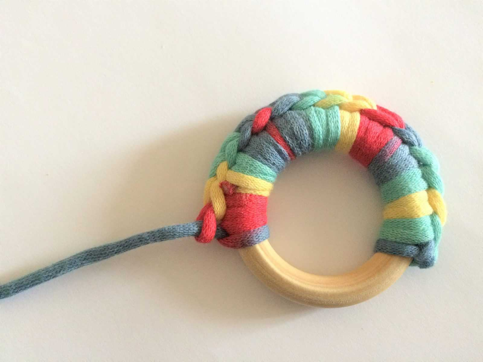 Crochet teether will colorful stitches around it.