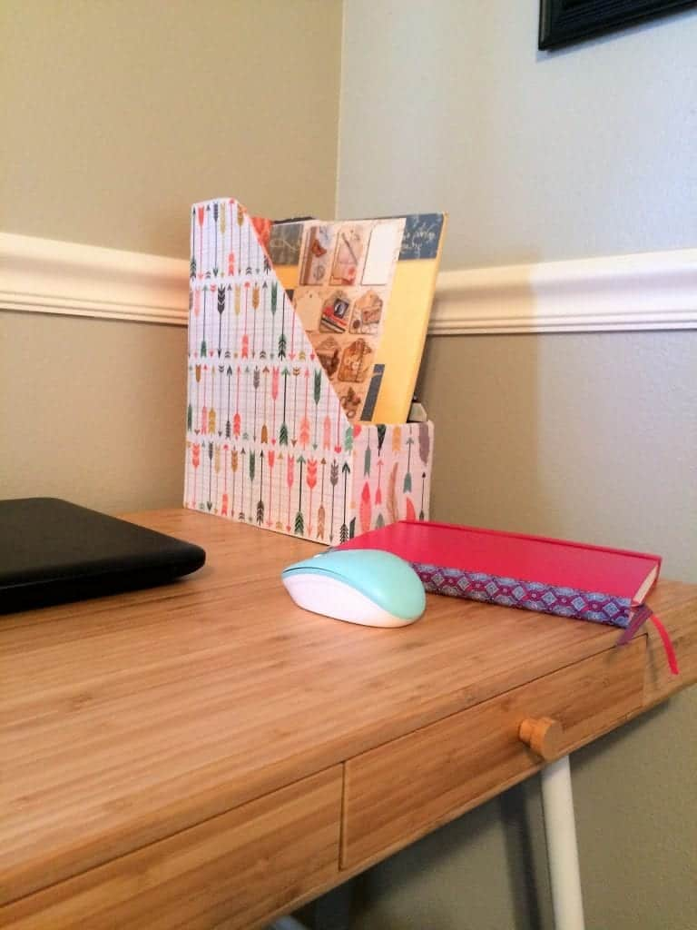 Magazine holder covered in decorative feather and arrow paper on desk.