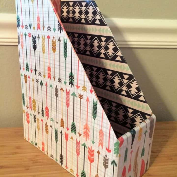 Paper covered book or magazine holder with blue stripes.