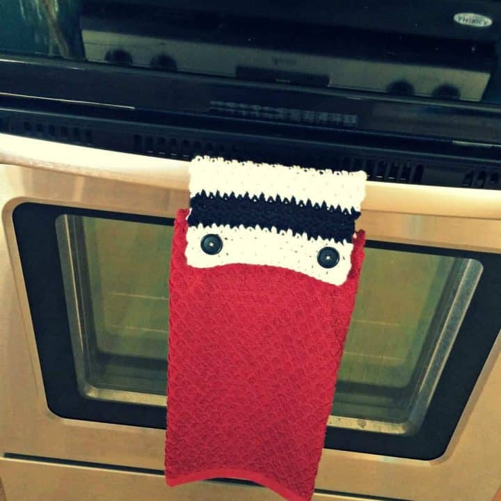 Red kitchen towel with striped crochet top buttoned on oven handle.