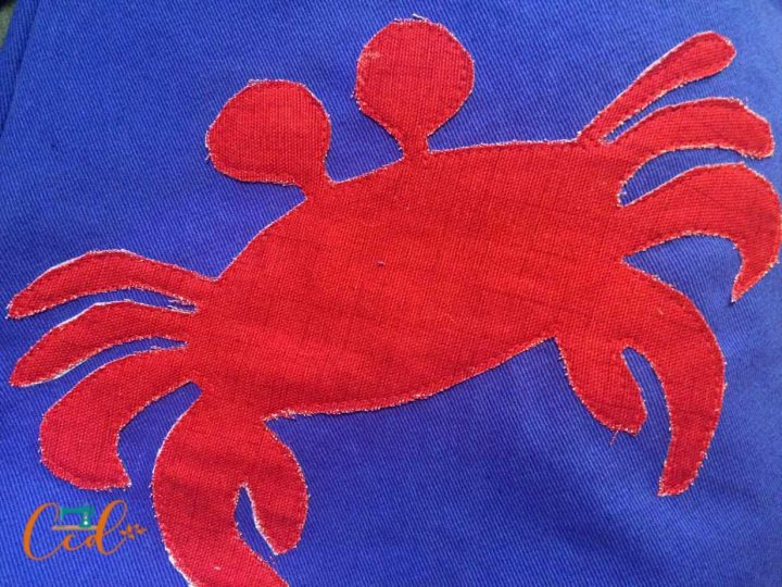 Crab in red sewn on by machine applique.
