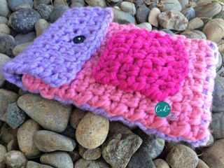 Pink and purple crochet tablet cover with pocket for ear buds.