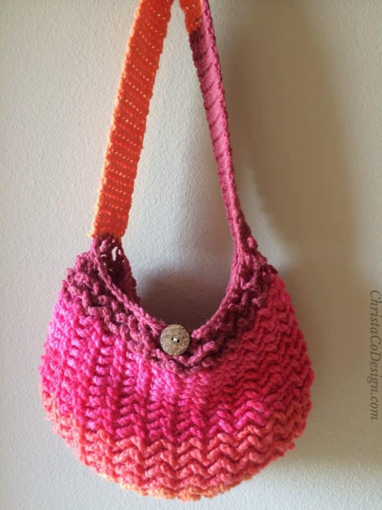 Complete One Skein Crochet Market Bag Pattern in pinks hanging on beige wall.