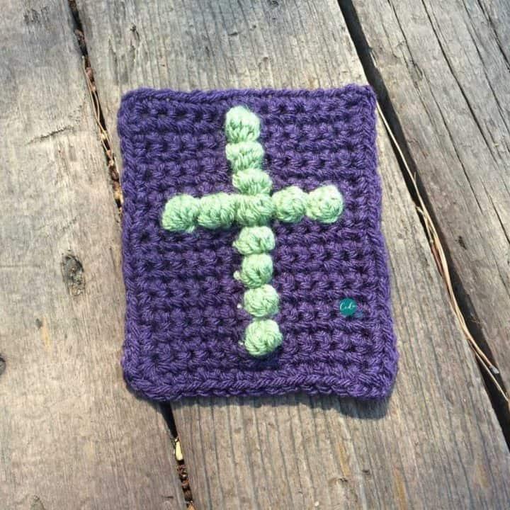Crochet cross on purple pocket size cloth.