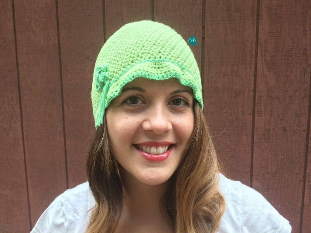 Woman with long brown hair smiling in lime green cloche hat.