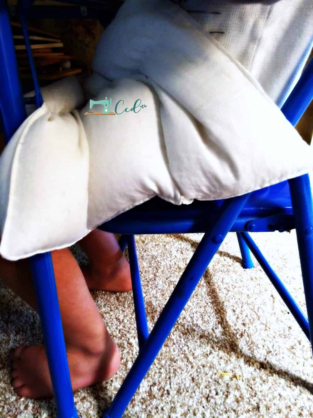 Weighted lap pad on lap in chair.