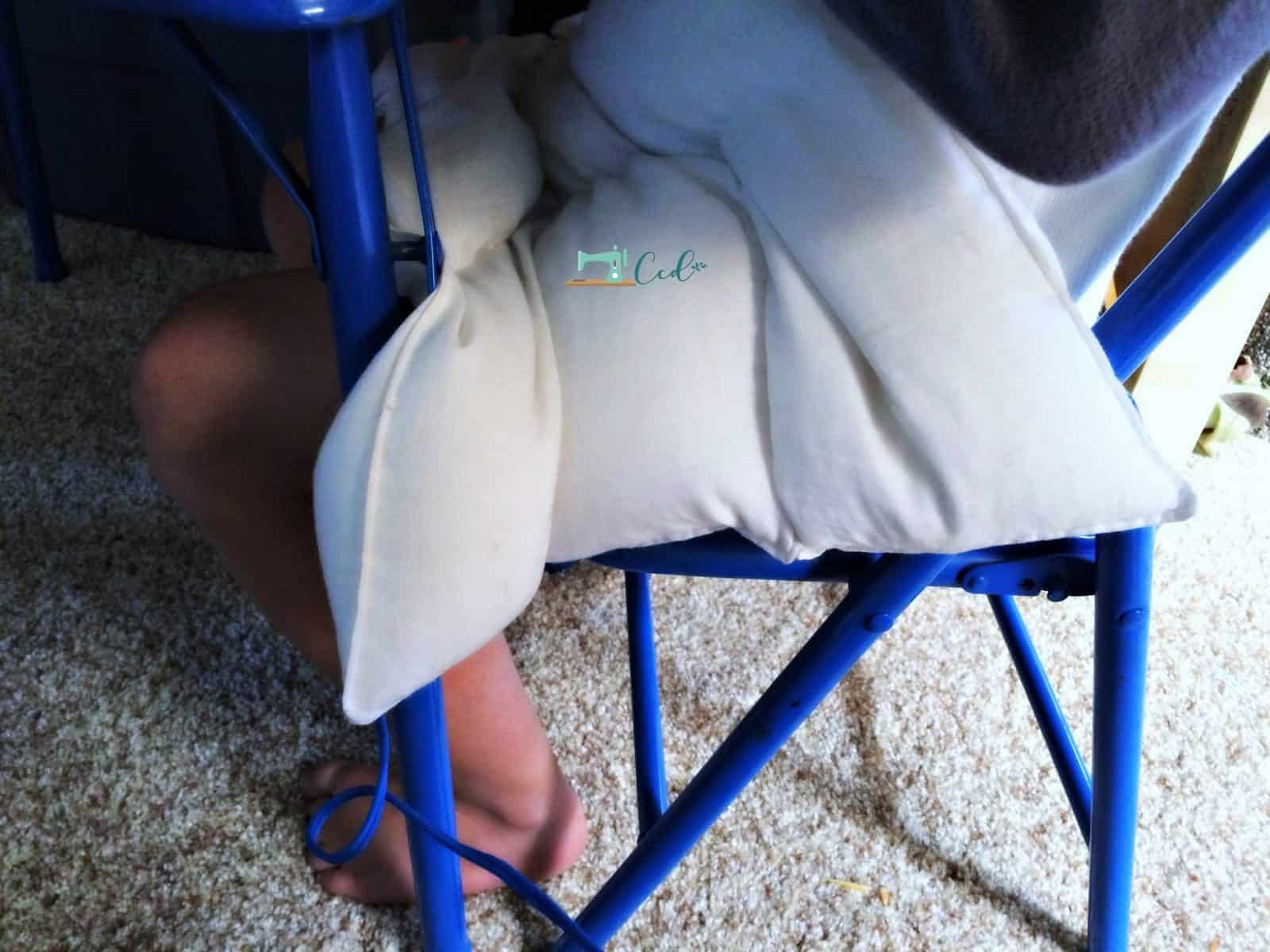 Weighted pad on lap in chair.