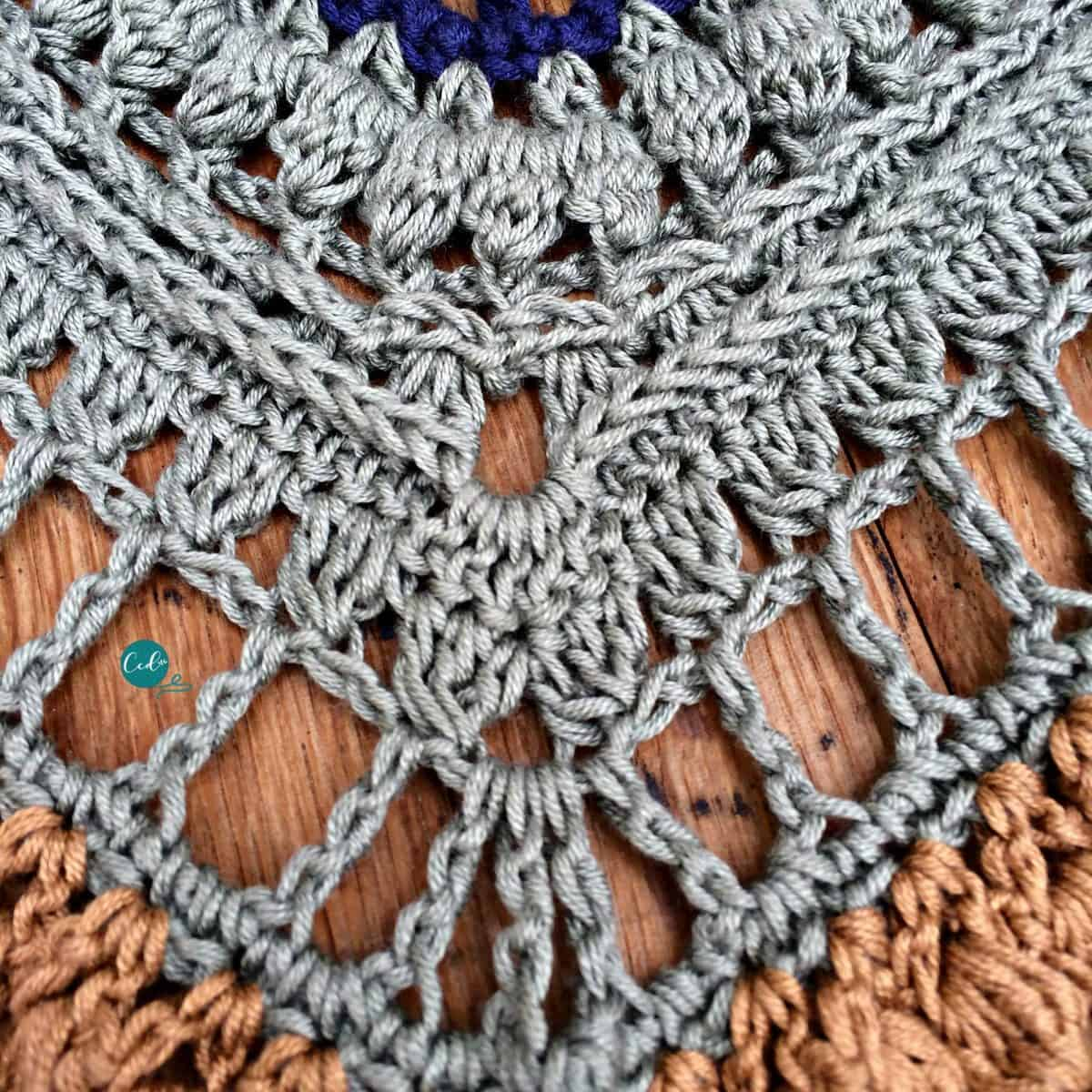 Close up of green rows repeating crochet shawlette stitches.