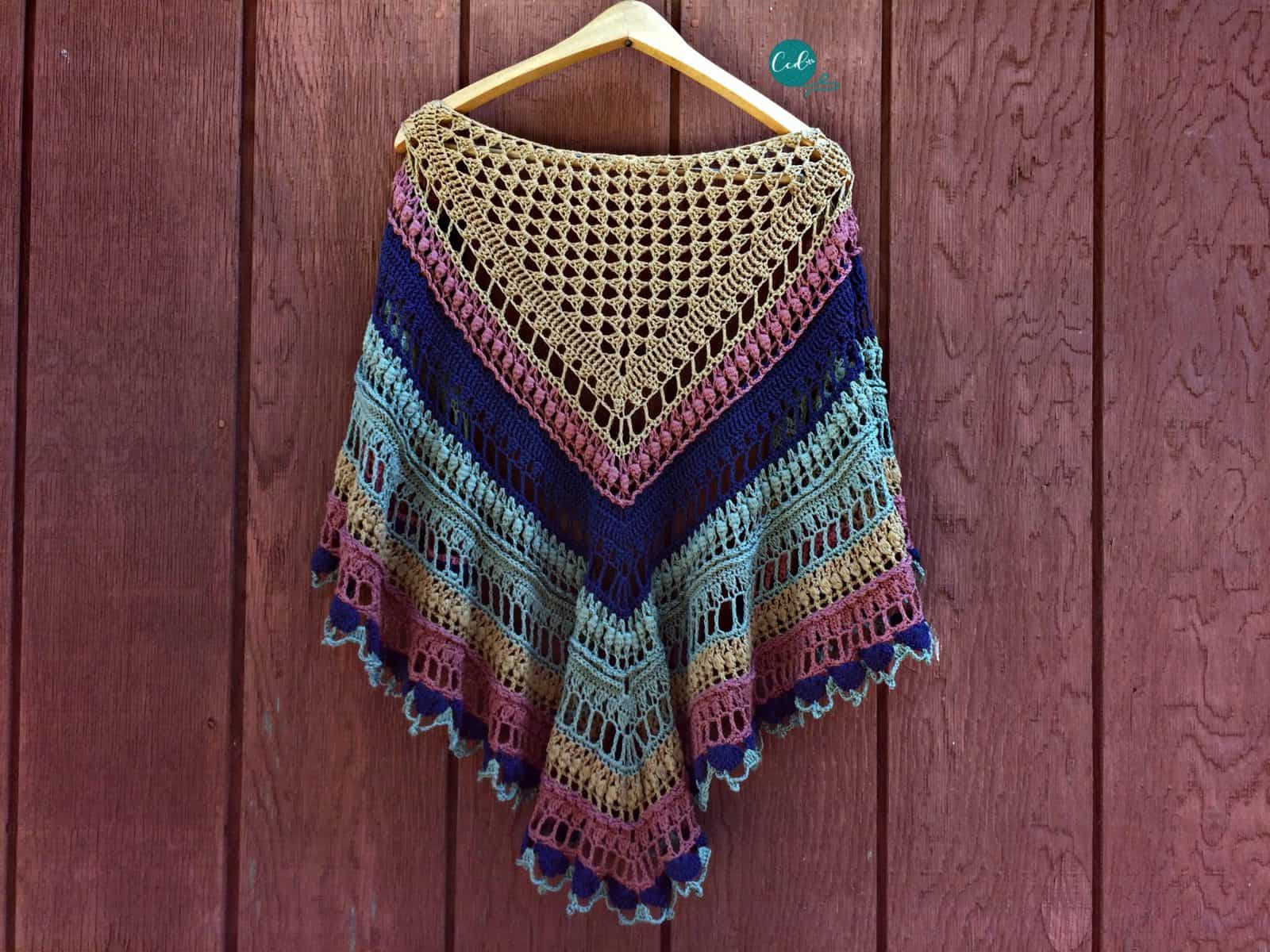 Crochet shawlette in browns, blues, greens and pink.