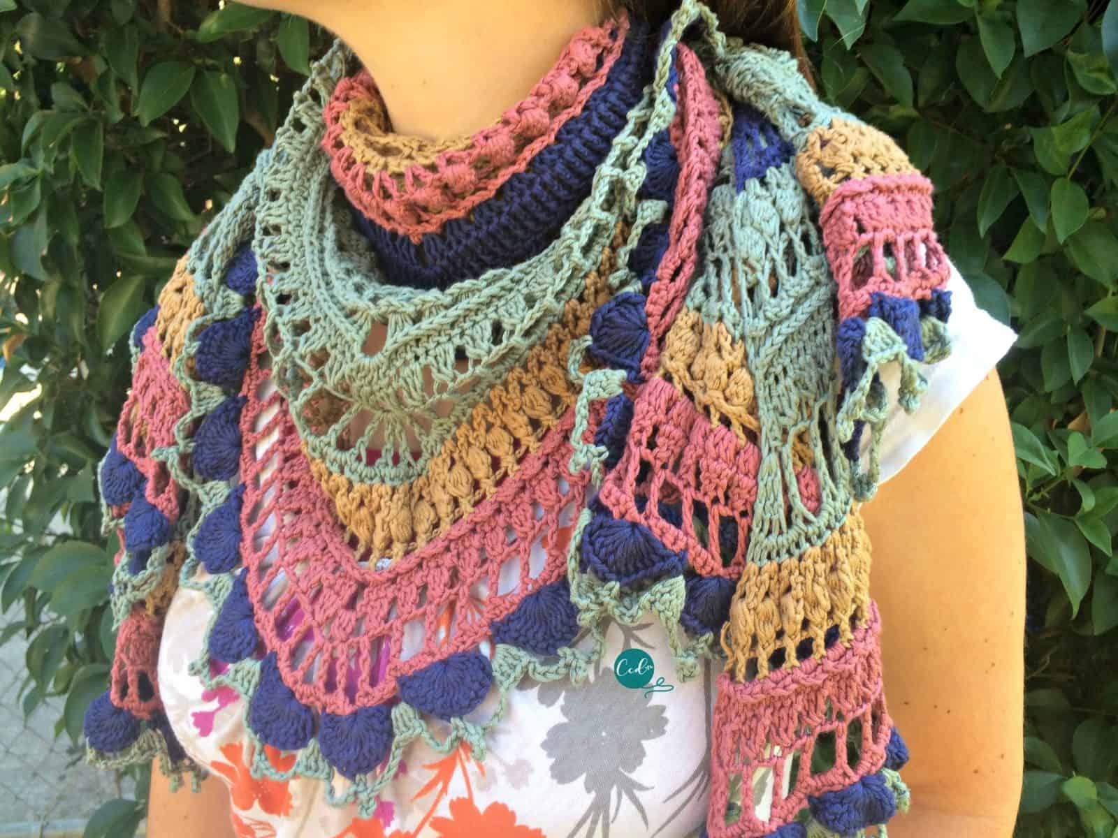 Crochet shawlette draped on woman's neck like triangle scarf.