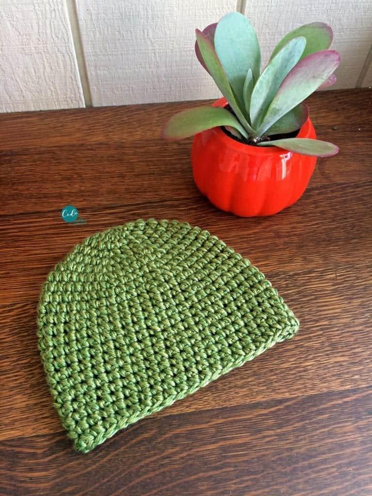 Crochet beanie laid flat on table.