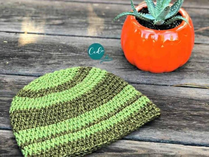 Green striped crochet beanie on wood patio.