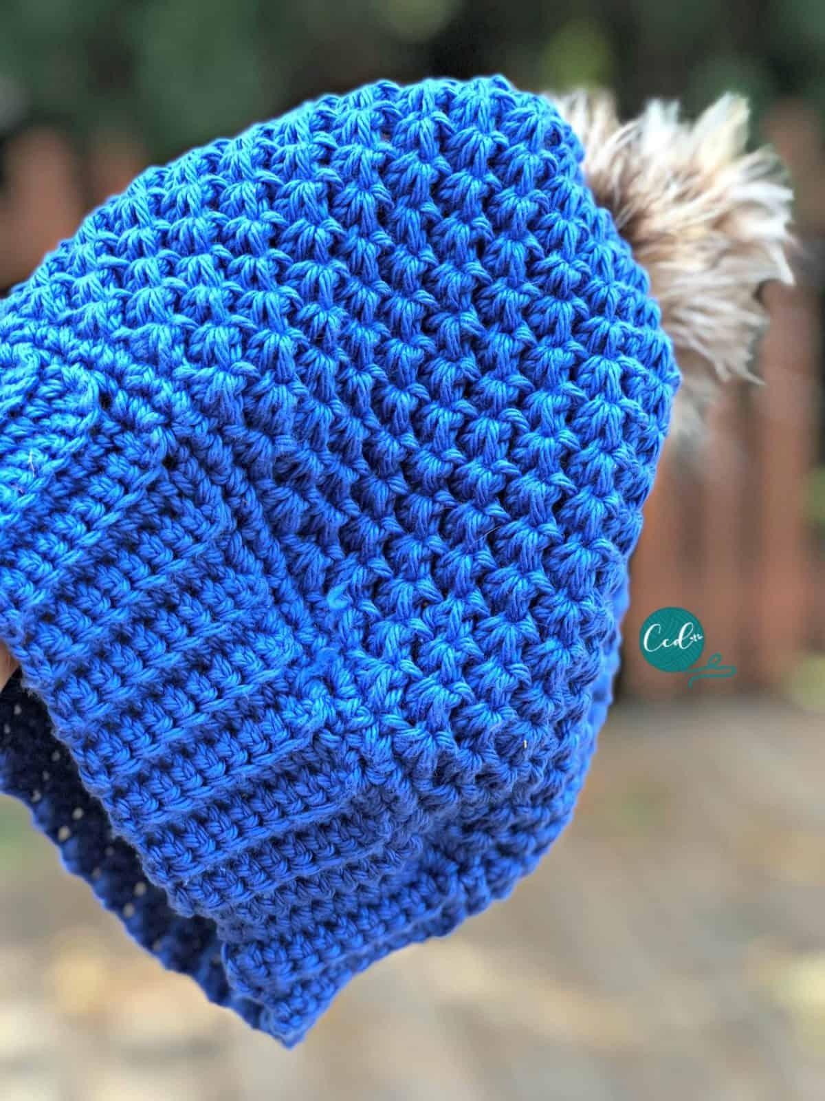 Blue crochet pom hat close up texture.