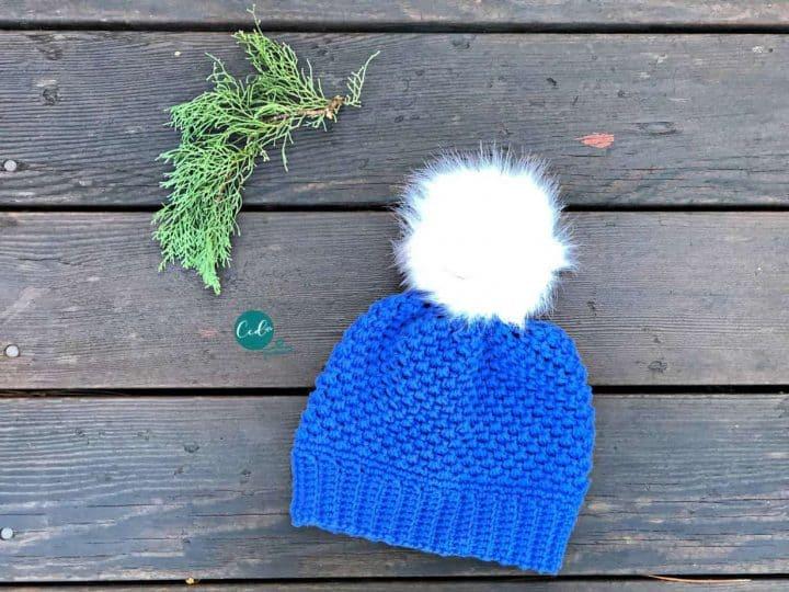 Textured crochet pom hat in blue.