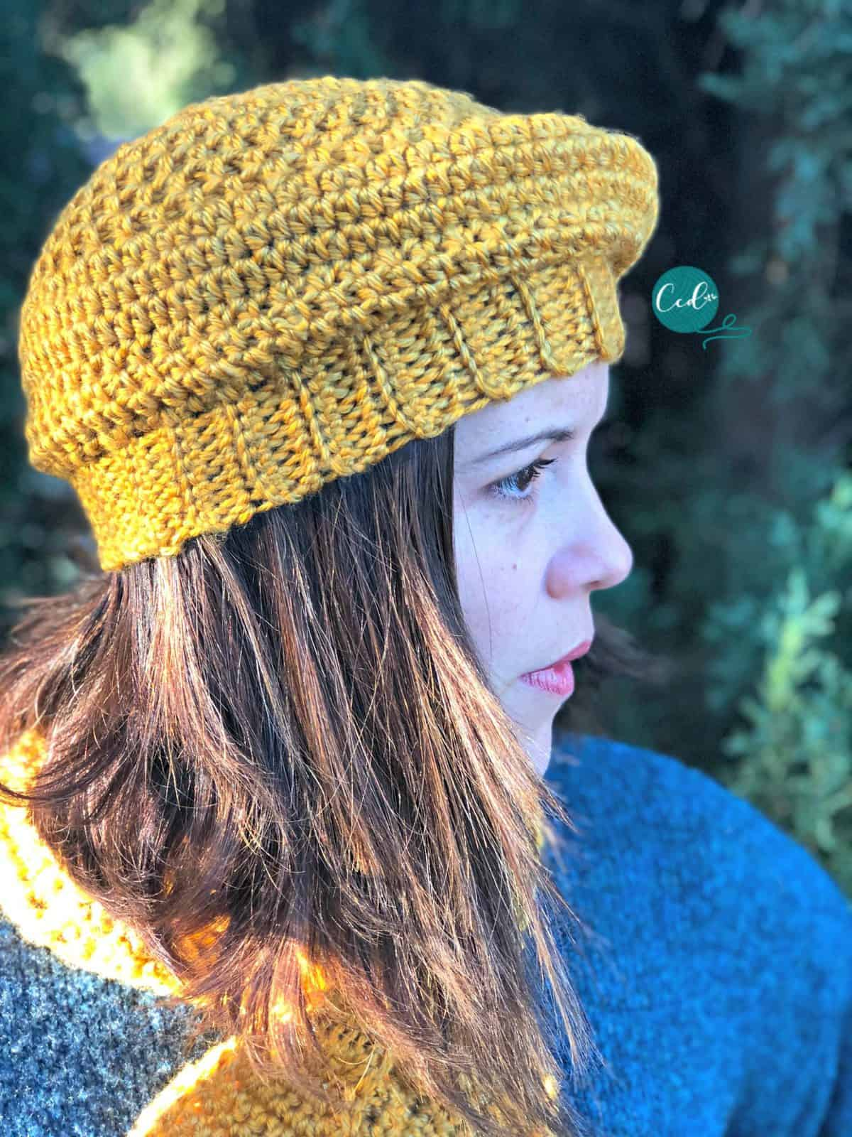Woman looking to side with yellow beret on.
