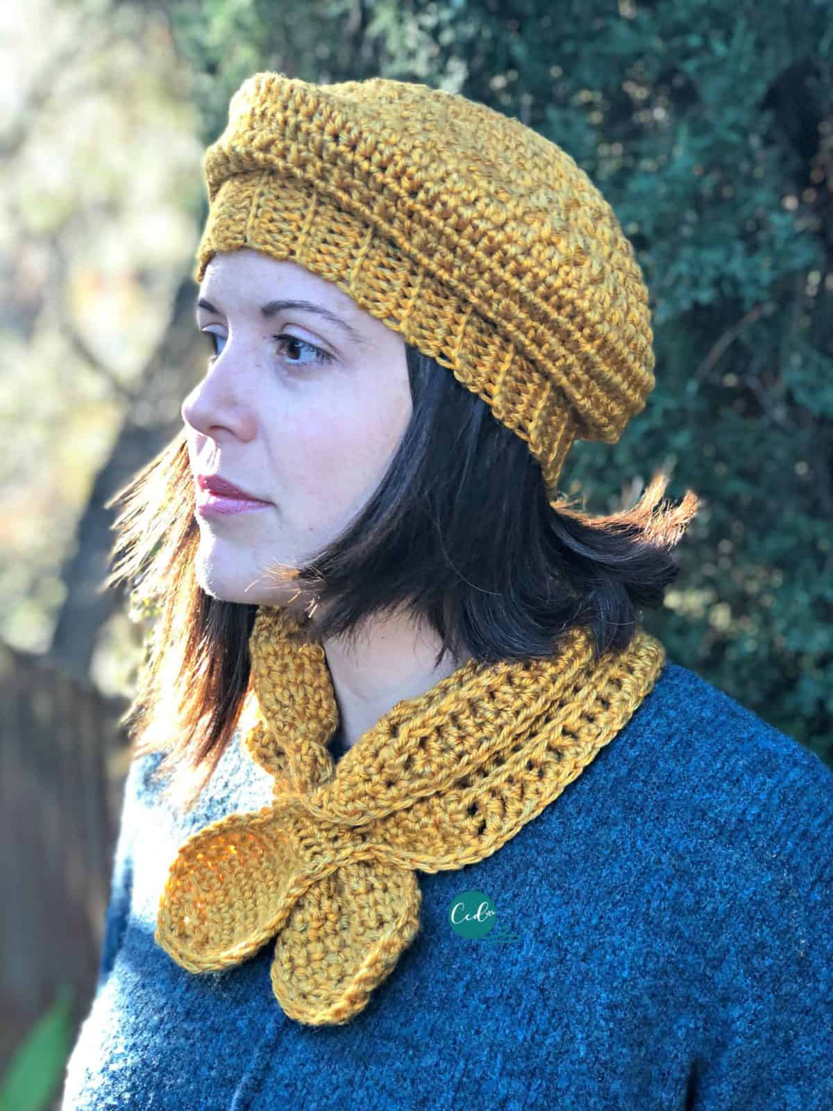 Woman in blue sweater looking out with mustard yellow crochet beret and scarflette on.
