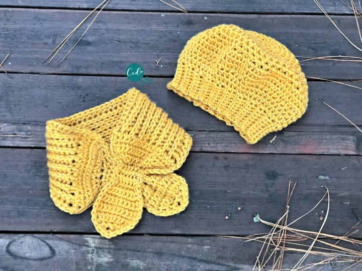 Finished mustard colored beret and scarflette laid flat on boards.