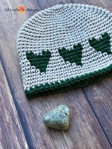 picture of grey hat with green hearts laid flat next to heart shaped rock