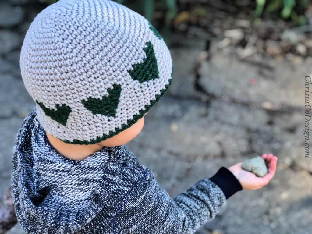 Boy in grey hat with green hearts holds heart shaped rock.