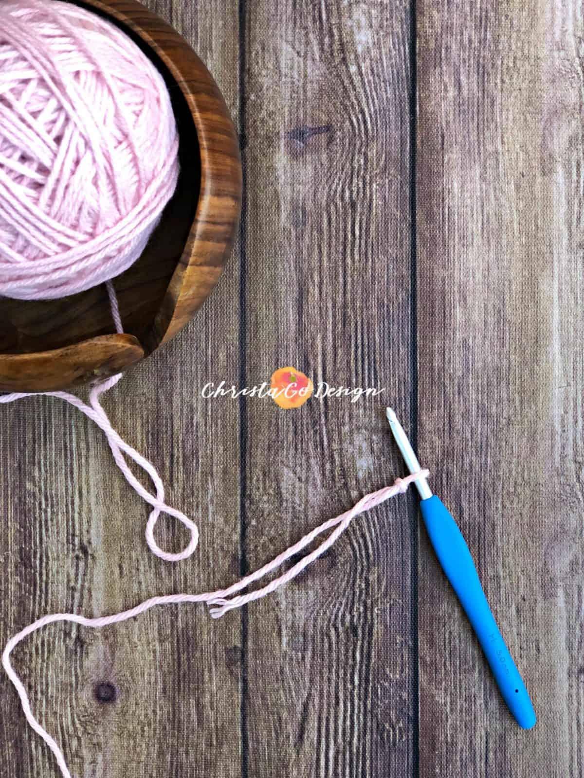Pink yarn on crochet hook.