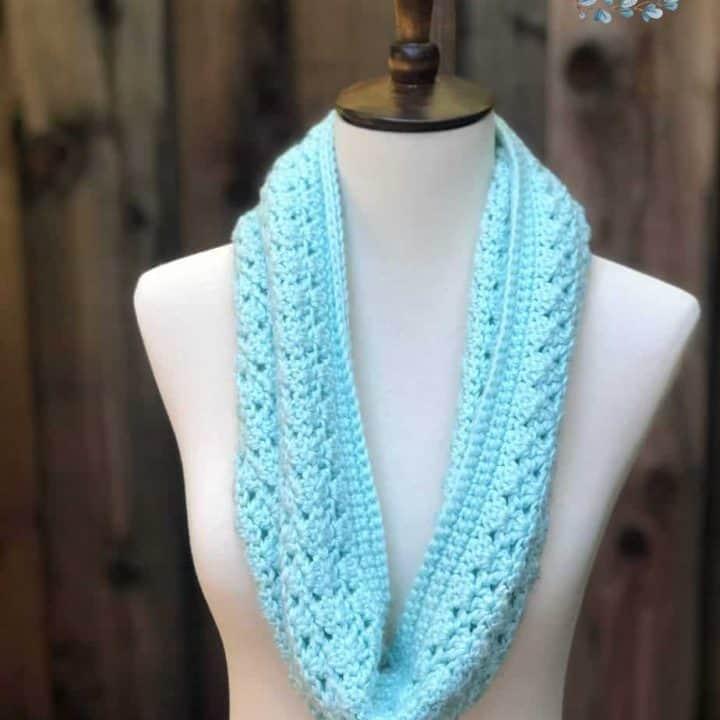 Blue crochet cowl styled in a single loop.