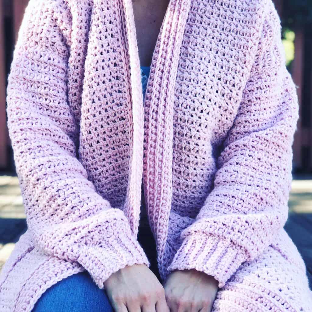Woman sitting in pink crochet cardigan.