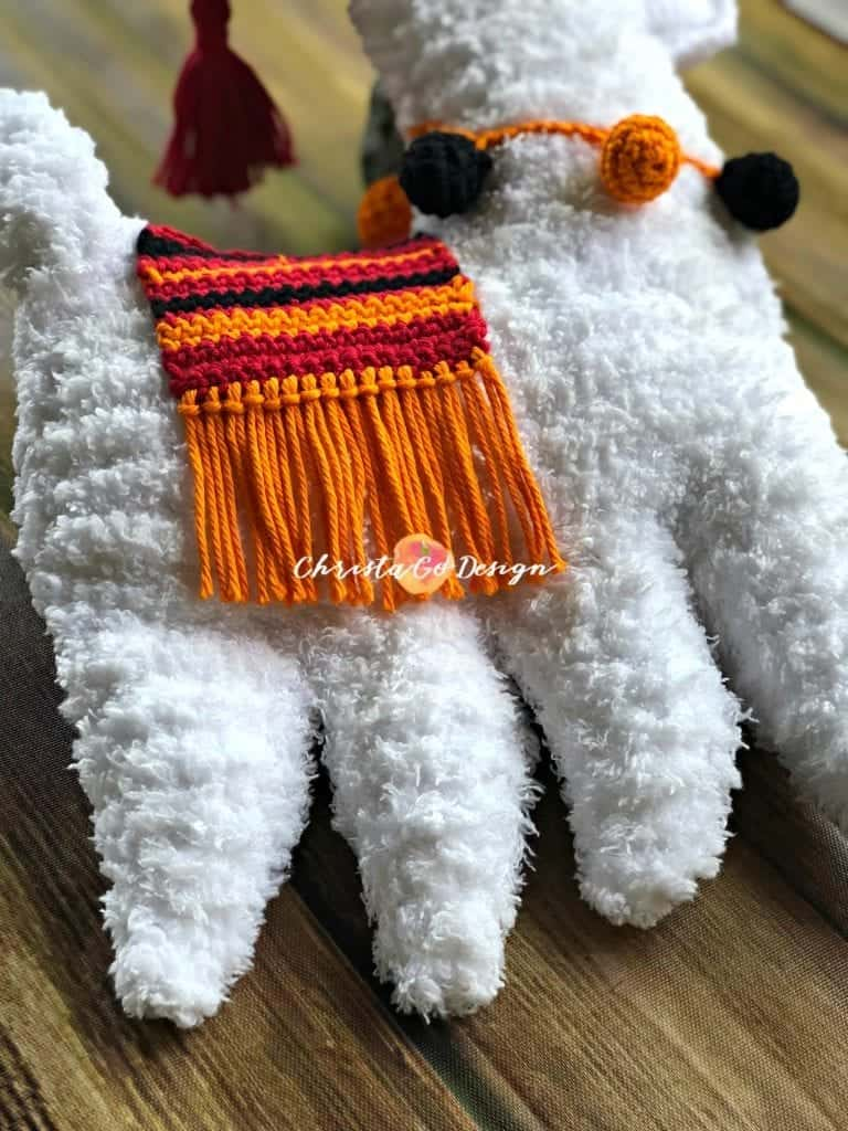 picture of fuzzy white crochet llama with orange red striped blanket