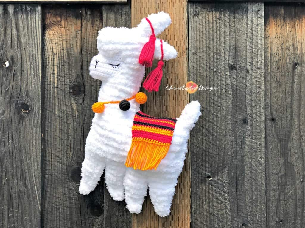 picture of fuzzy llama with orange blanket and baubles