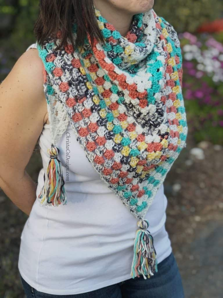 Woman in white with color granny triangle scarf crochet pattern with tassels.
