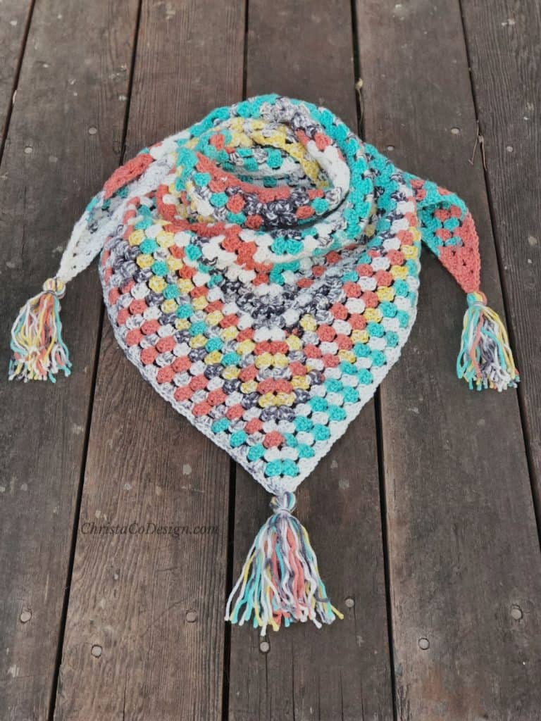Crochet triangle scarf from granny triangle with tassels laid on wood porch.