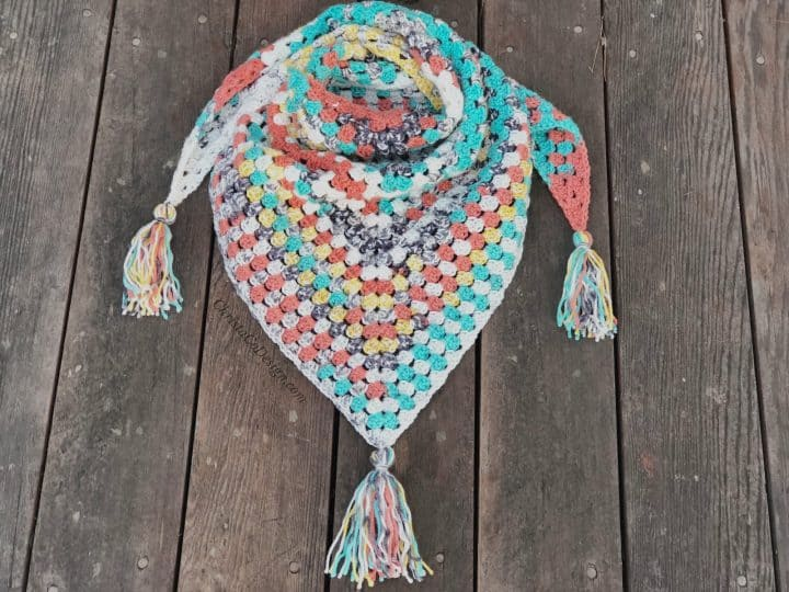 Colorful scarf triangle pattern with tassels crochet on wood back drop.