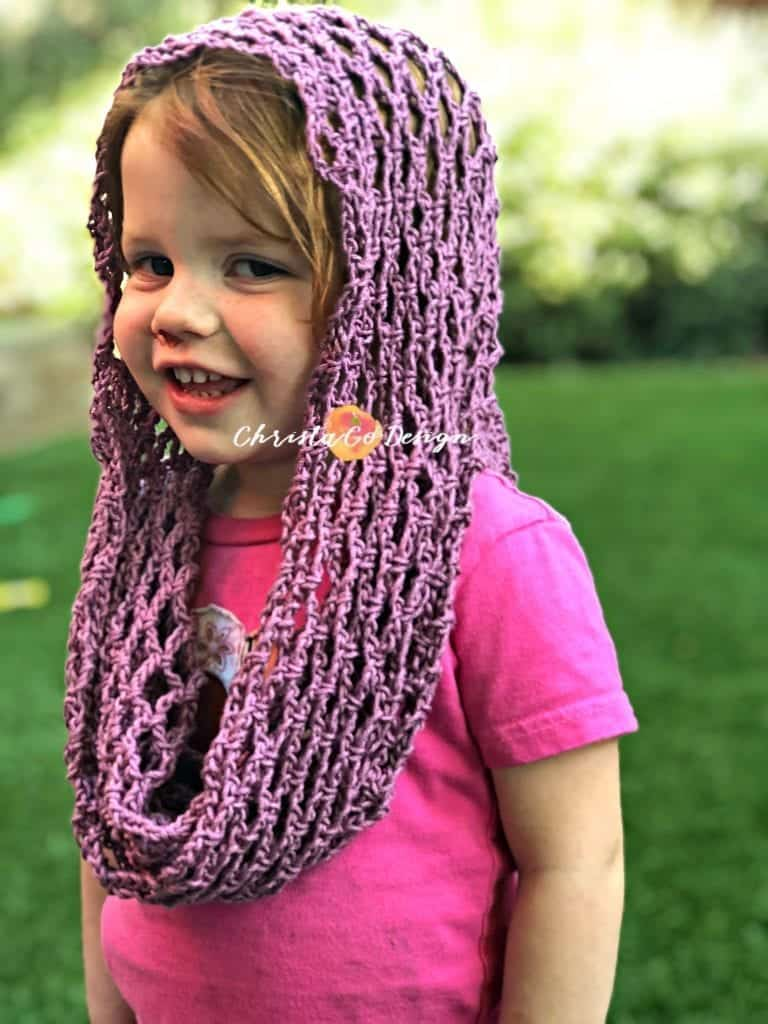 picture of toddler smiling with crochet cotton cowl draped on head