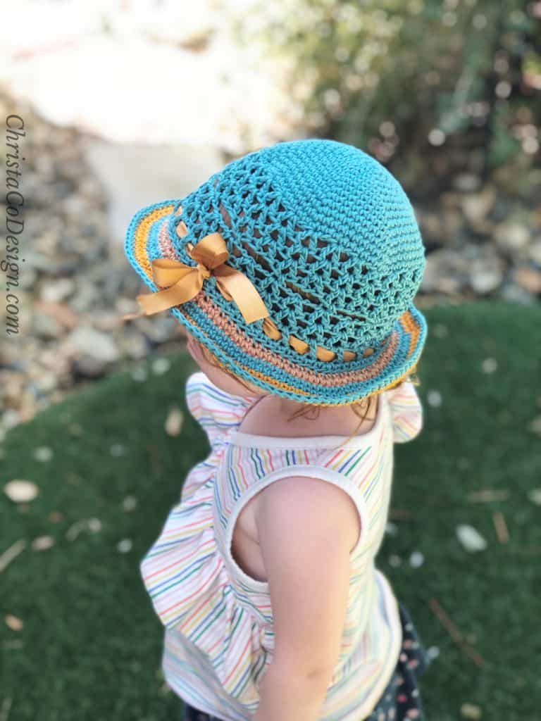 Girl is teal sun hat with bow.