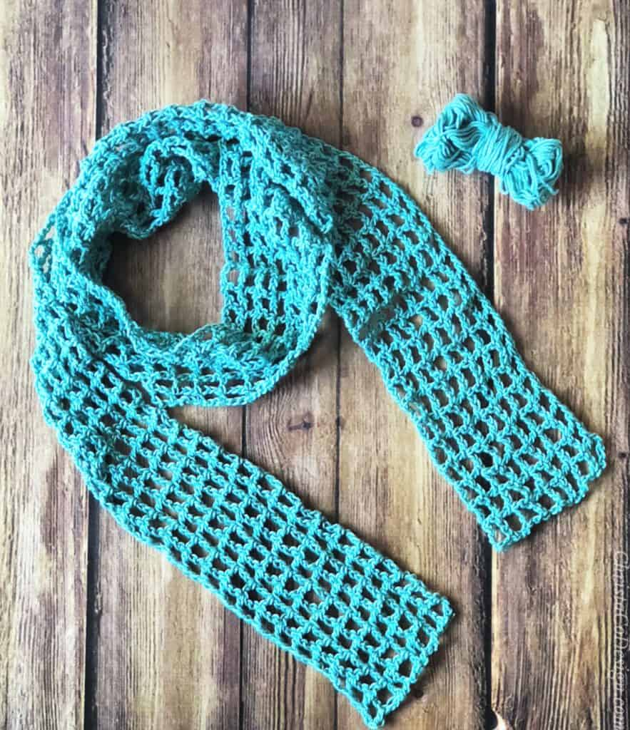 Teal skinny crochet scarf circle draped on wood background with one ball of yarn in teal.