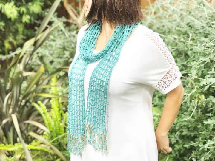 Woman outside in garden in white with crochet lace skinny scarf in teal with fringe on.