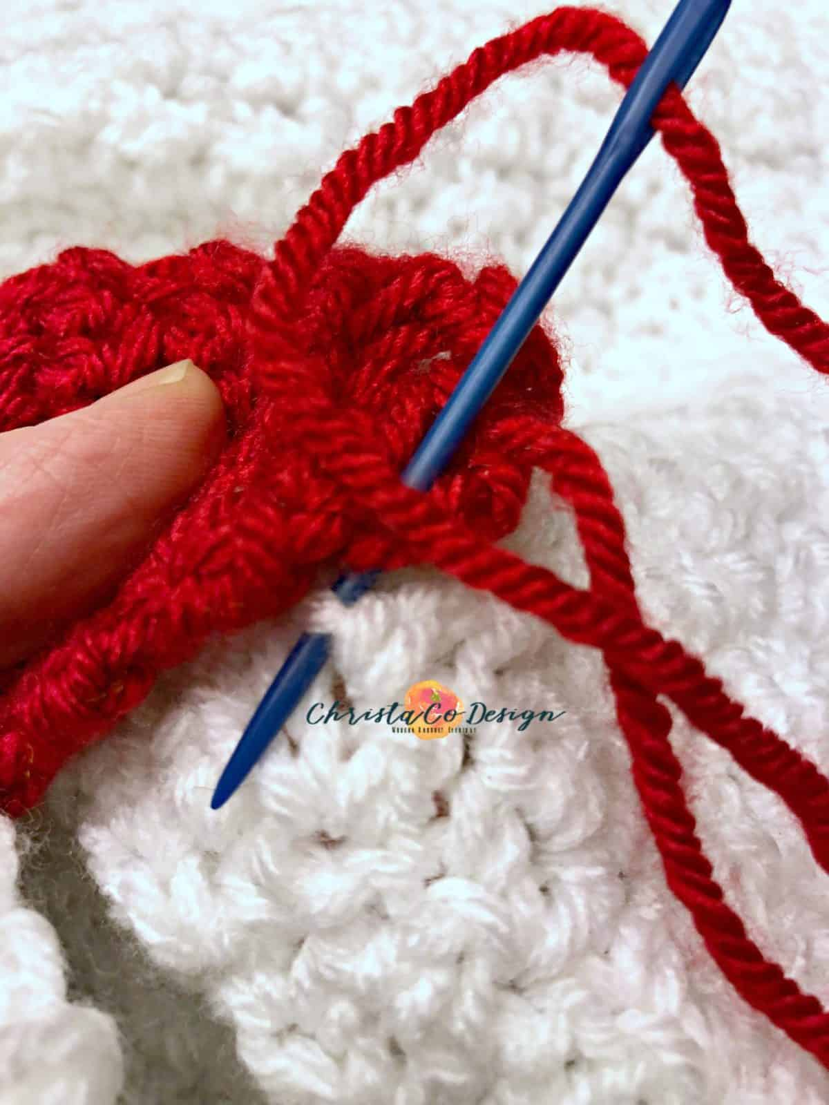 picture of blue yarn needle threaded with red yarn matching the Christmas light to appliqués on to white blanket