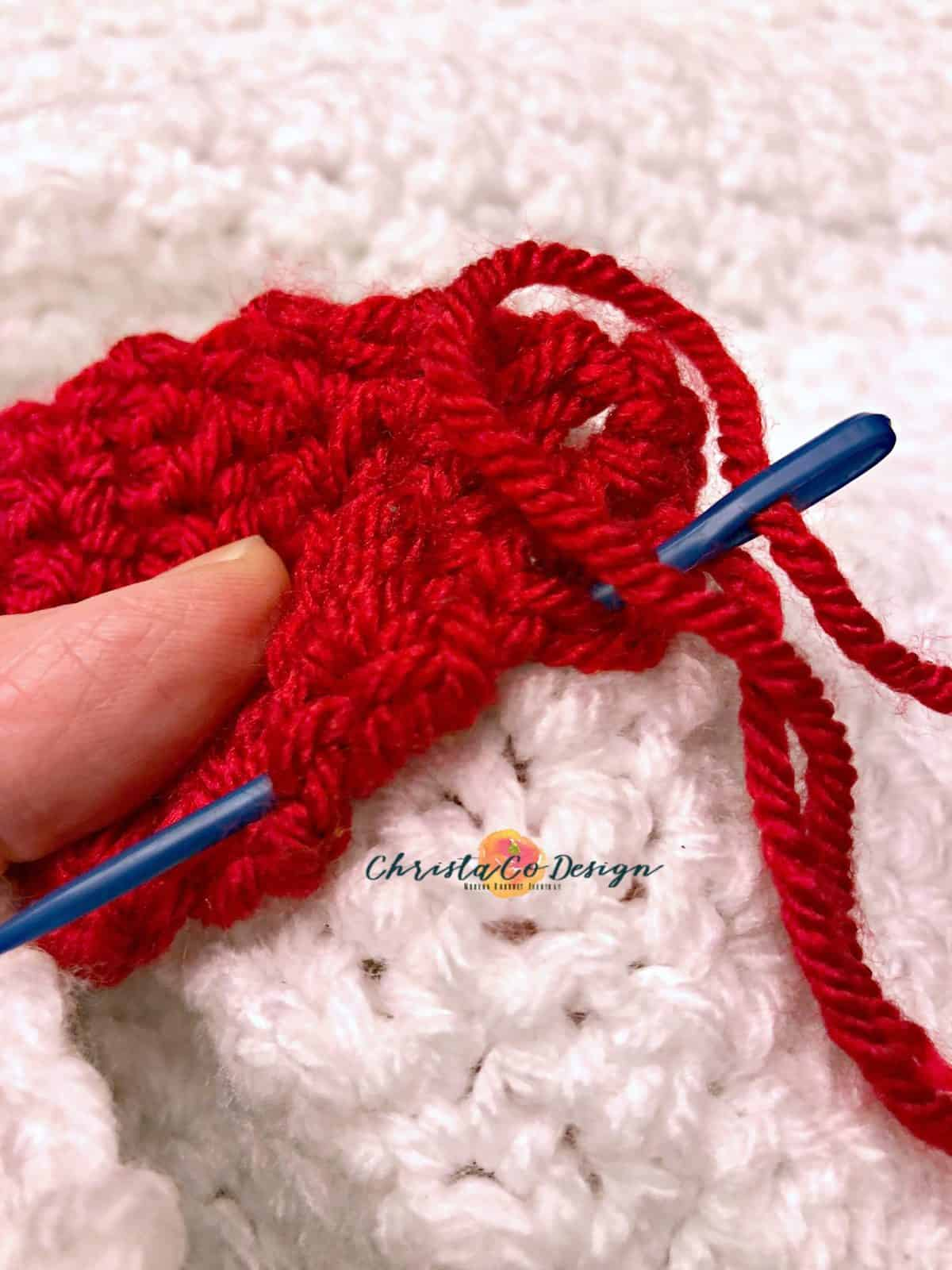 picture of blue yarn needle sewing through red crochet christmas light on to white blanket