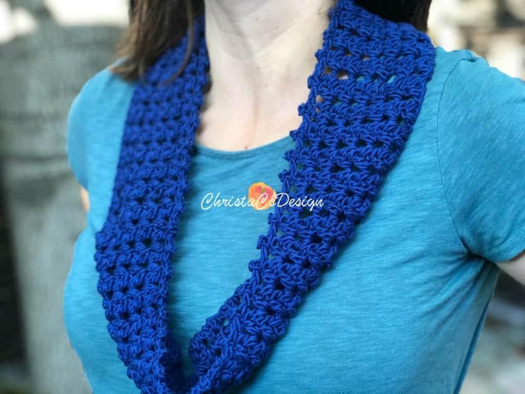 Textured blue crochet cowl around neck.