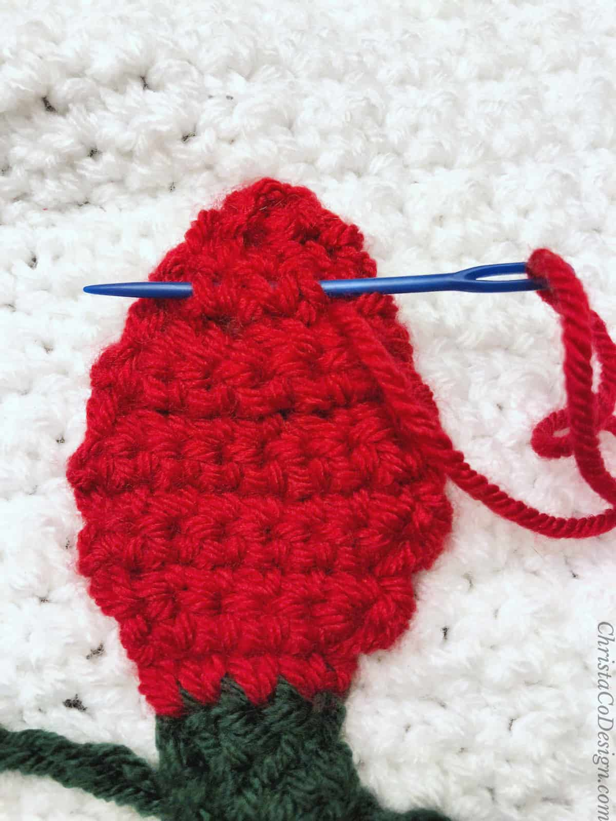 Red crochet Christmas light with blue needle through it.