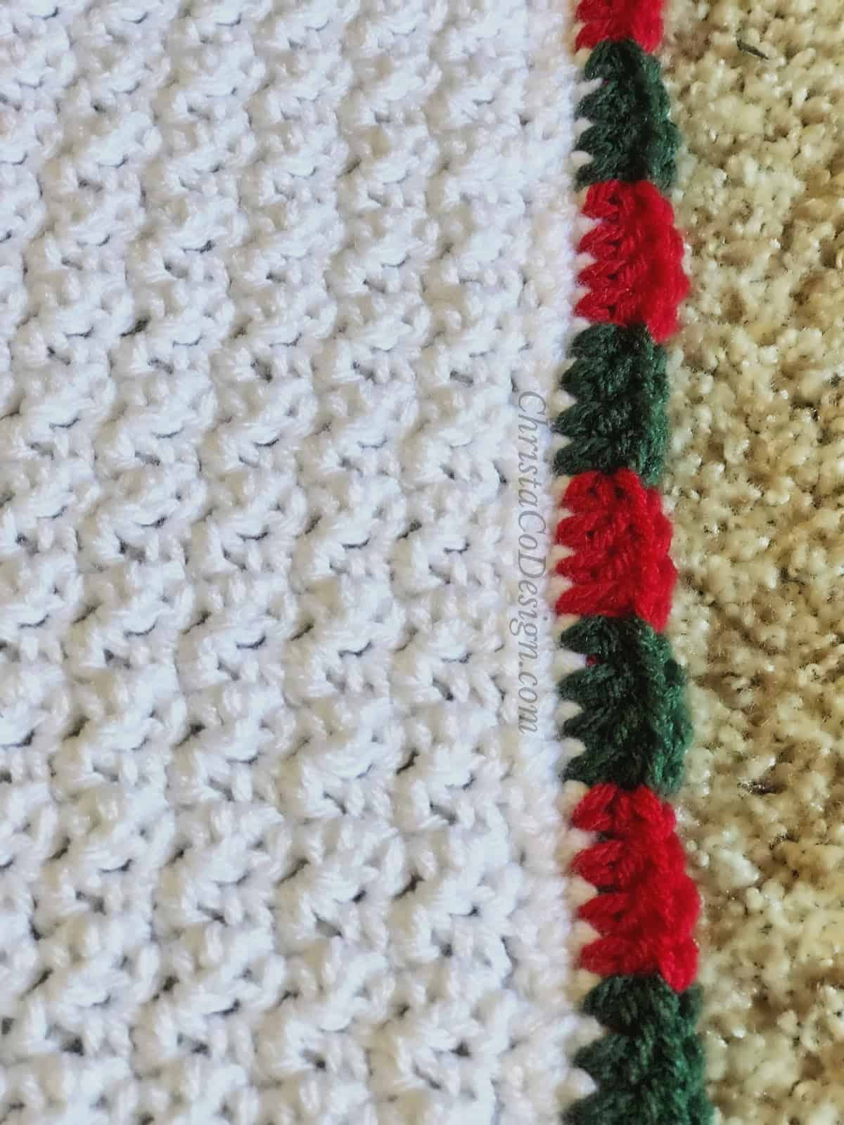 Red and green double crochet border on blanket.