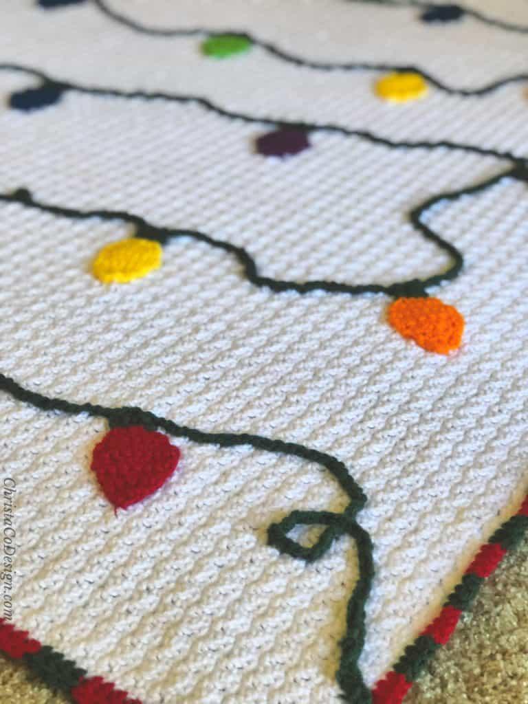 Crochet Christmas lights blanket crochet pattern in colorful lights.