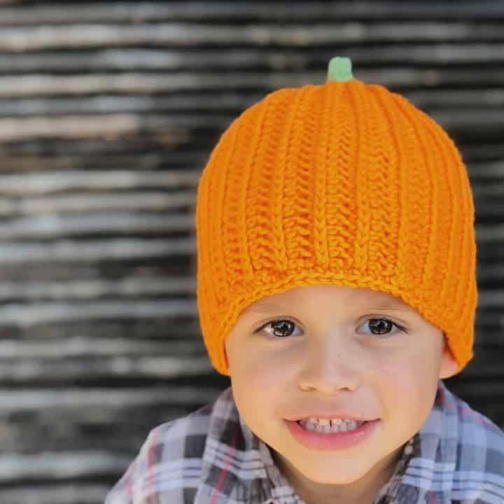 Crochet pumpkin hat pattern in orange on preschooler.