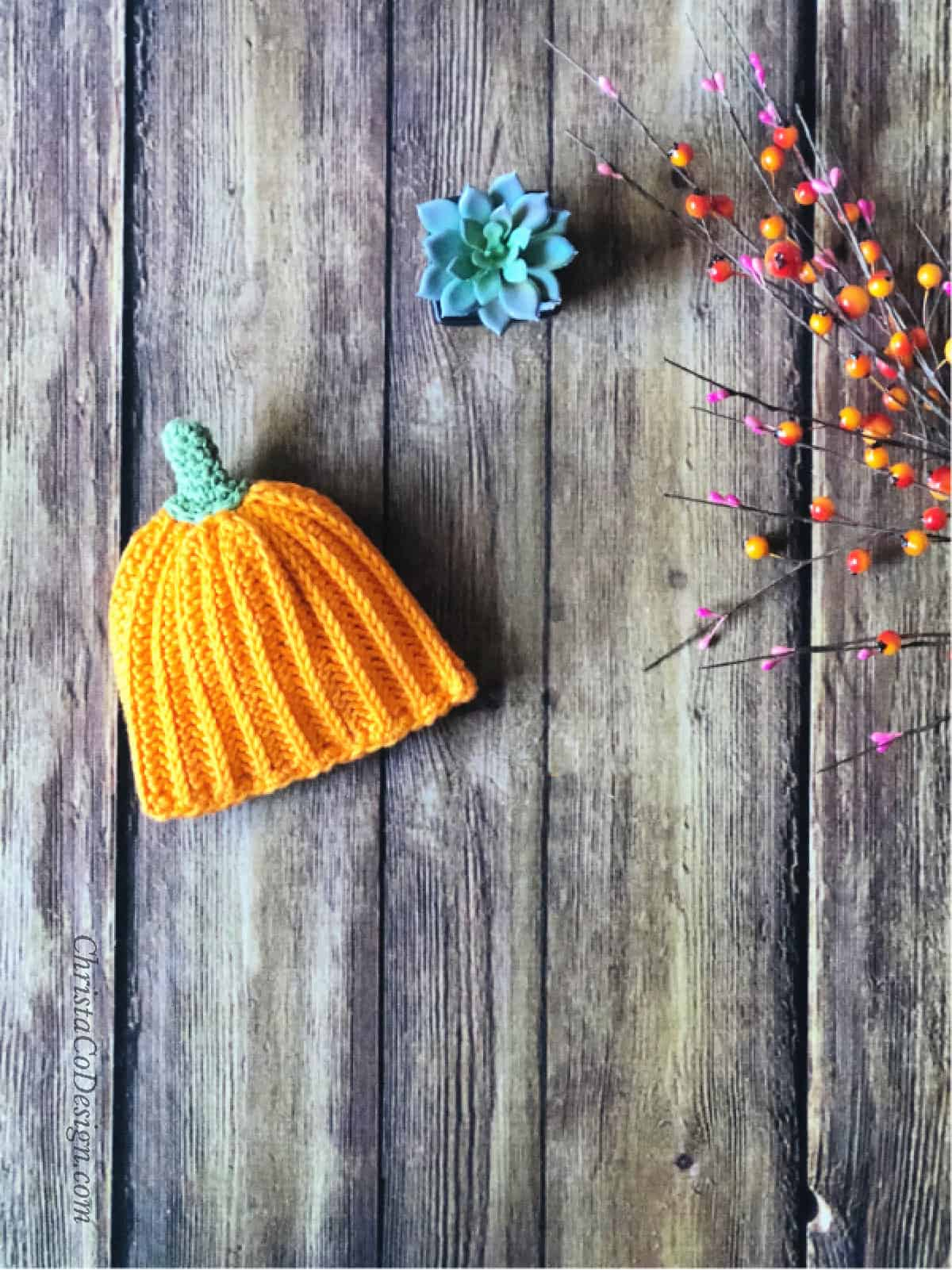Crochet pumpkin hat for baby in orange on wood backdrop.