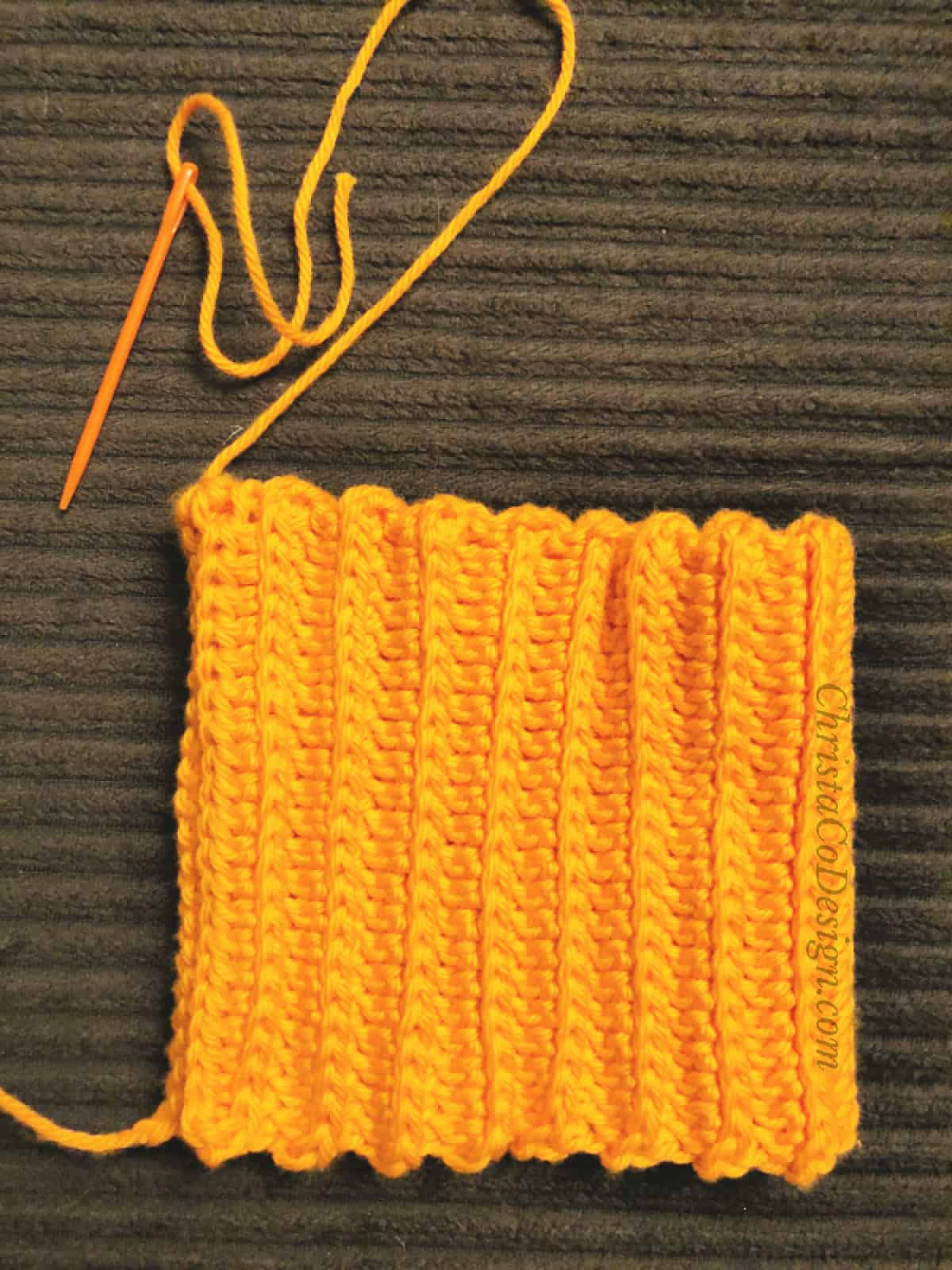 Fabric folding and seaming orange crochet rectangle for pumpkin hat.
