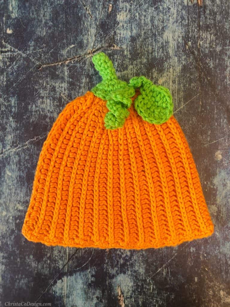 Orange ribbed crochet pumpkin hat pattern with green stem, leaf and vine.