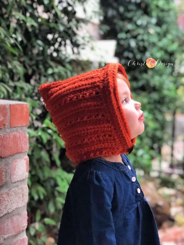 picture of toddler looking into rain with crochet pixie hat on