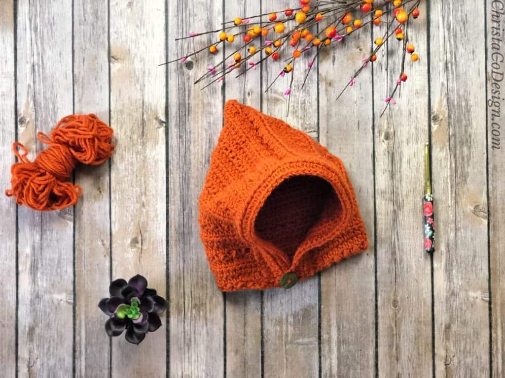 Crochet pixie hat pattern in rusty orange flat with wood background.