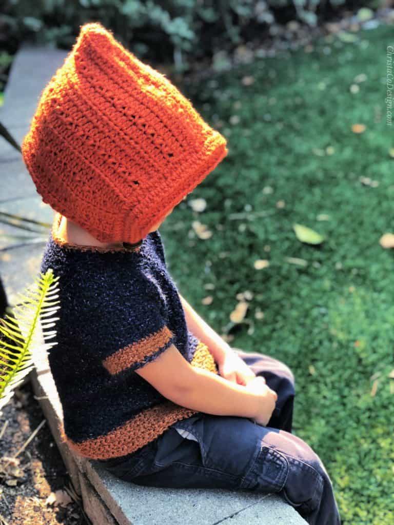 Boy looks down outside in crochet pixie hat pattern.